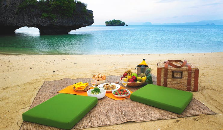 Picnic laid out on sandy beach with green seating cushions, a picnic basket and blue sea in the background