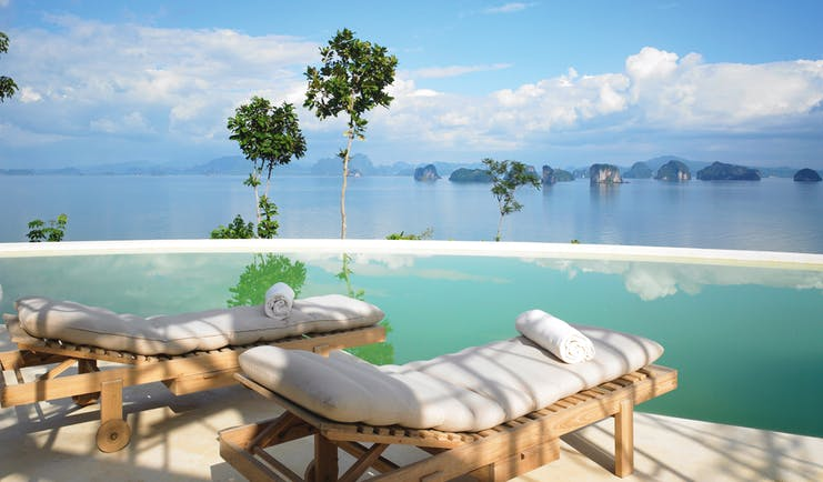Two sun beds laid out by an infinity pool looking out over the sea