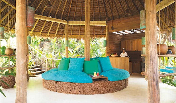 Six Senses Yao Nai spa juice bar in beach hut with blue and green sofa seating area, palm trees in the background and a wooden bar