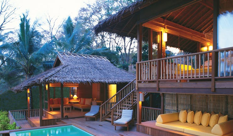 Exterior view of a villa at the Six Senses Yao Nai with a large rectangular pool, wooden decking, seating areas, a cream couch and wooden stairs leading up to the suite