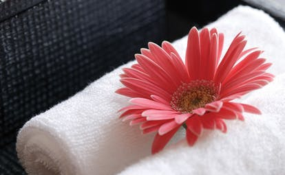 The Dhara Devi Thailand pink flower close up on white towels