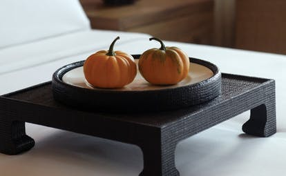 The Dhara Devi Thailand suite bedroom close up shots of miniature pumpkins on tray on bed