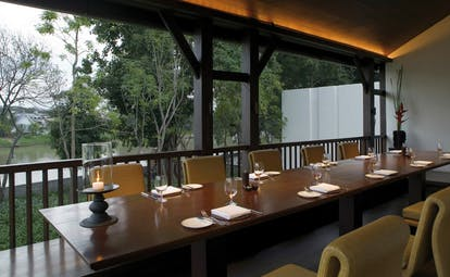 The Dhara Devi Thailand upper restaurant terrace covered outdoor dining area long table river view