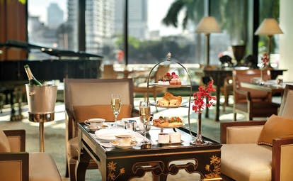 The Peninsula Bangkok Thailand afternoon tea with champagne in lounge with grand piano and city views