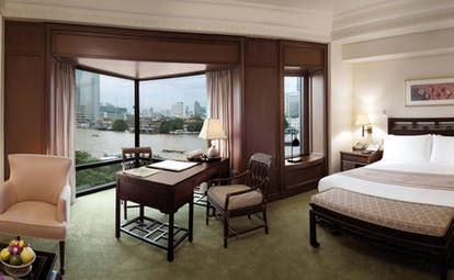 The Peninsula Bangkok Thailand deluxe room bedroom sitting area large windows with river and city view