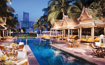 The Peninsula Bangkok Thailand outdoor pool loungers wood pagodas terrace dining city views