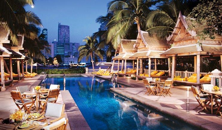 The Peninsula Bangkok Thailand outdoor pool loungers wood pagodas terrace dining city views