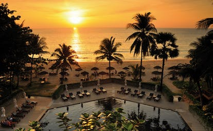 The Surin Phuket Thailand aerial outdoor pool hexagonal pool loungers beach view at sunset