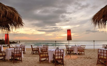 The Surin Phuket Thailand beachfront dining tables and chairs on the beach