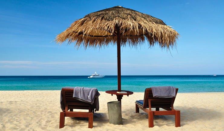 The Surin Phuket Thailand ocean view beach sun loungers thatched umbrellas yacht