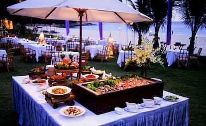 The Surin Phuket Thailand outdoor buffet evening dining beach view