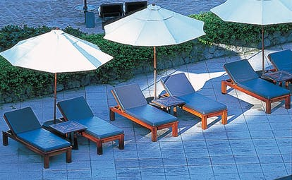 The Surin Phuket Thailand poolside sun loungers and umbrellas
