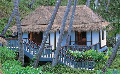 The Surin Phuket Thailand traditional bungalow thatched roof steps trees greenery