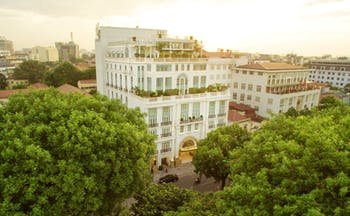 Apricot Hotel exterior, grand hotel building, colonial style architecture, trees, city in background