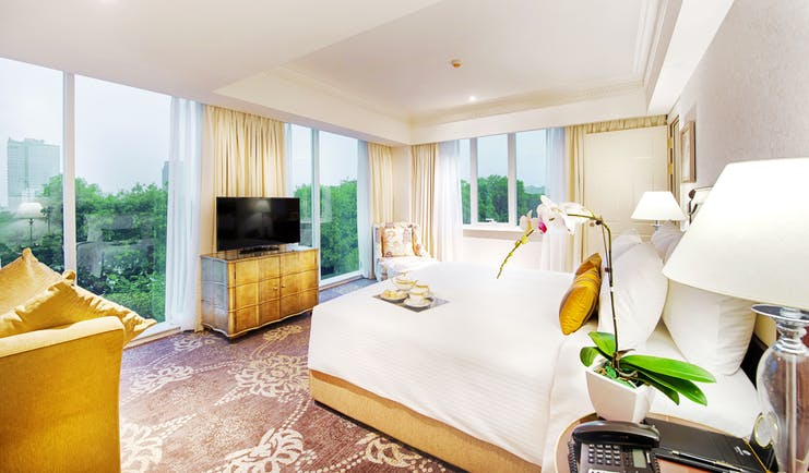 Apricot Hotel masterpiece suite bedroom, double bed, television, elegant decor, large windows with city views