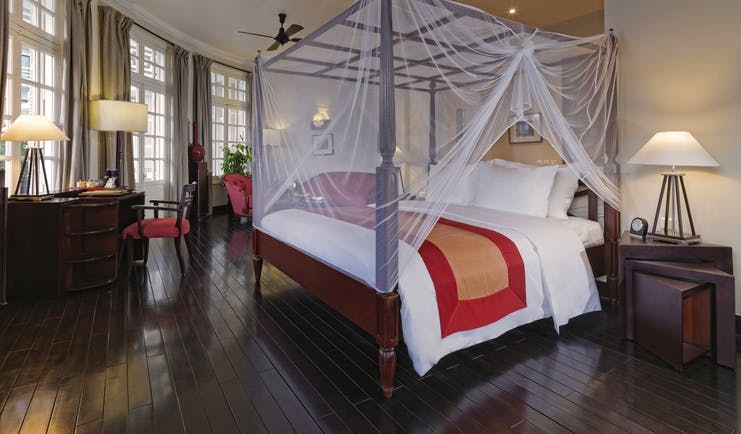 Azerai La Residence colonial suite, bed with canopy traditional decor, colonial style