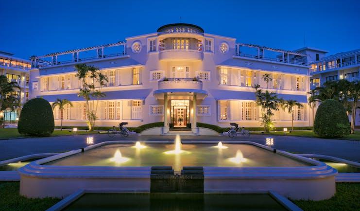 Azerai La Residence hotel exterior, fountain, gardens, hotel lit up at sunset