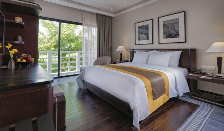 Azerai La Residence superior standard guestroom, bed, french windows leading to balcony, elegant decor