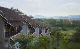 Belmond La Residence Phou Vao exterior, hotel buildings overlooking gardens, mountains in background
