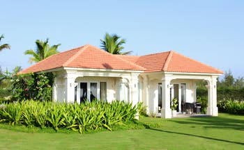 Boutique Hoi An beach villa exterior with terrace and garden with neat lawns and foliage