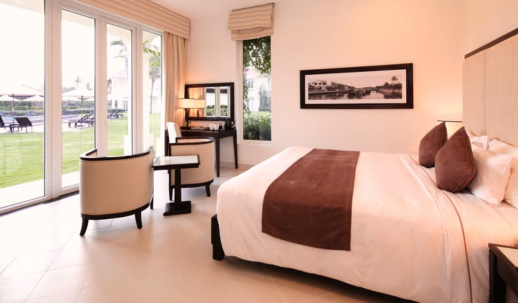 Boutique Hoi An premier deluxe room, bed, bright modern decor, doors leading to garden