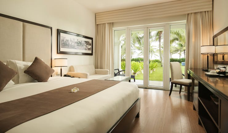Boutique Hoi An villa bedroom, double bed, desk, modern decor, french doors leading to garden
