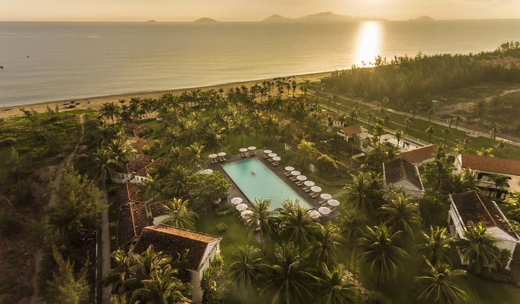 Boutique Hoi An resort aerial shot, villas, pool, beach in background, palm trees and greenery