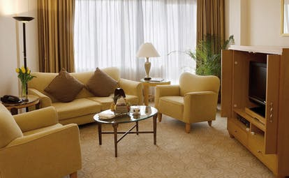 Caravelle Hotel Vietnam signature suite lounge sofas armchairs and television