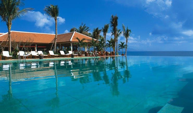 Evason Ana Mandara Resort Vietnam infinity pool lounger palm trees