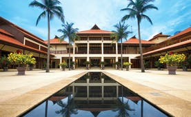 Furama Resort Vietnam building with white portico and two palms behind narrow pool