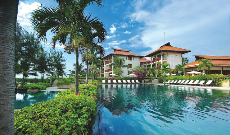 Furama Resort Vietnam large blue swimming pool with palm trees and white and red roofed building of 3 floors