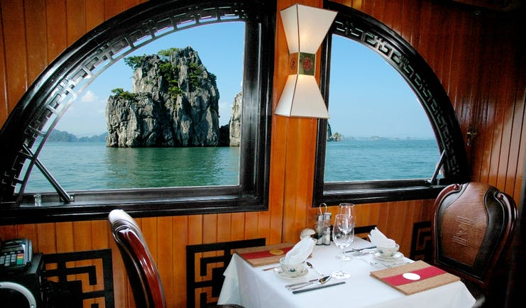 L'Amour Junk dining room, table set for two, window with view out onto bay