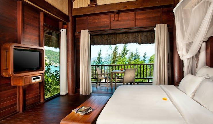 L'Ayla Ninh Van Bay hill rock villa bedroom, double bed with canopy, television, wood panel walls