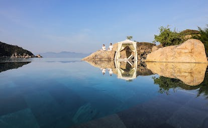 L'Ayla Ninh Van Bay infinity pool with mountains in background, couple meditating on rock