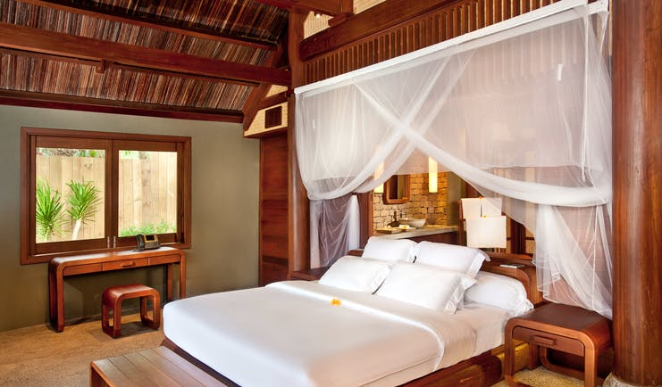 L'Ayla Ninh Van Bay lagoon villa bedroom, double bed with canopy, wooden panelling and decor