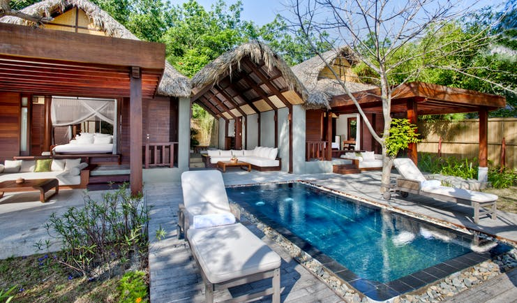 L'Ayla Ninh Van Bay lagoon villa exterior, pool, sun loungers, trees in background