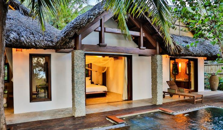L'Ayla Ninh Van Bay villa exterior, pool, thatchted roof, palm trees, lit up bedroom
