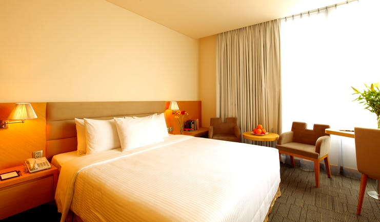 Liberty Central Saigon signature deluxe room, double bed, chairs, large windows, modern decor