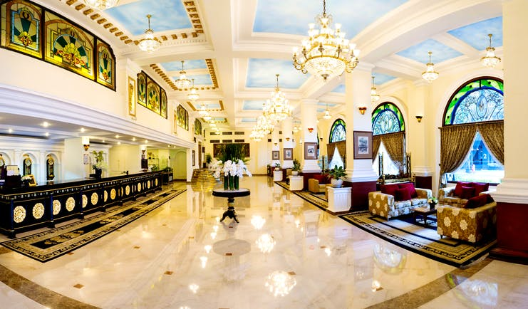Majestic Hotel Saigon lobby, dark wooden desks, marble floors, chandelier, grand decor