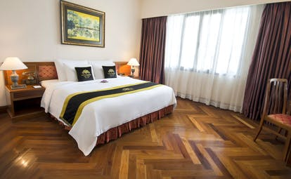 Majestic Hotel Saigon president suite, large double bed, wooden floor, bright modern decor