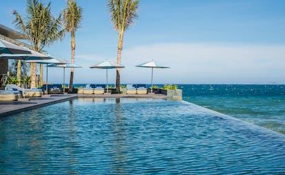 Mia Nha Trang infinity pool, overlooking beach and sea, poolside loungers and umbrellas