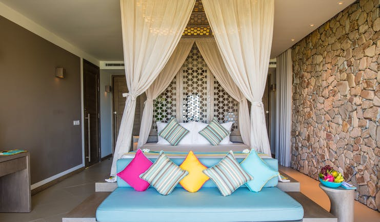 Mia Nha Trang Resort villa bedroom, double bed with canopy, sofa at end of bed, colourful modern decor
