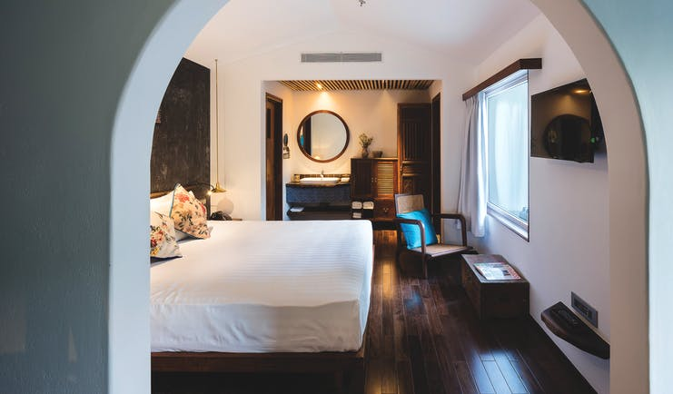 City room at the Myst Dong Khoi in Vietnam with a large archway entrance, big double bed, television, wooden floors and double doors leading into a bathroom