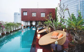 Pool view with large rectangular pool, seating pods set up around on wooden decking and plants