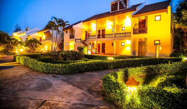Palm Garden Resort exterior, hotel buildings lit up at night, pathways through neat gardens