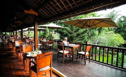 Palm Garden Resort terrace, outdoor dining area, tables, chairs, umbrellas, overlooking garden