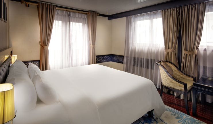 Paradise Luxury Cruise paradise suite, double bed, drapred windows, traditional decor