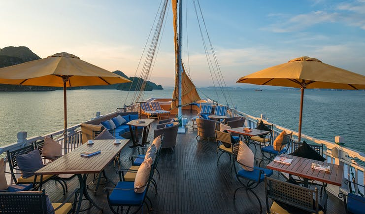 Paradise Luxury Cruise sun deck, tables and chairs on top deck of boat, views over the sea