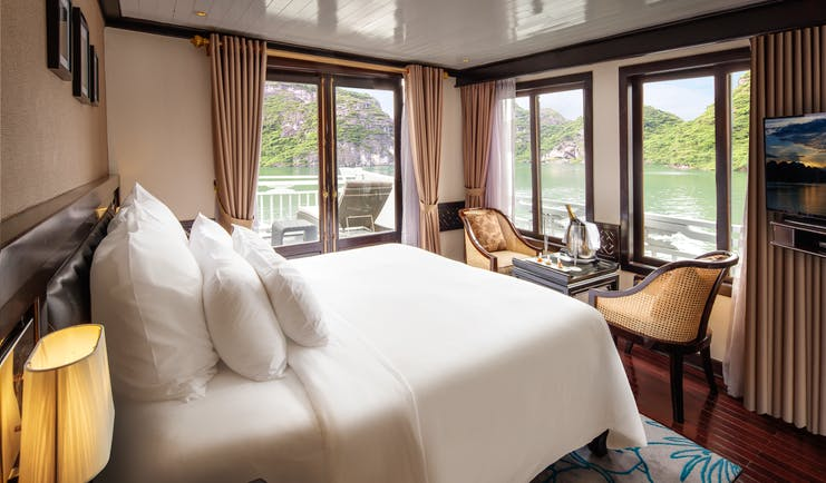 Paradise Luxury Cruise terrace suite, double bed, table and chairs, windows overlooking sea, traditional decor