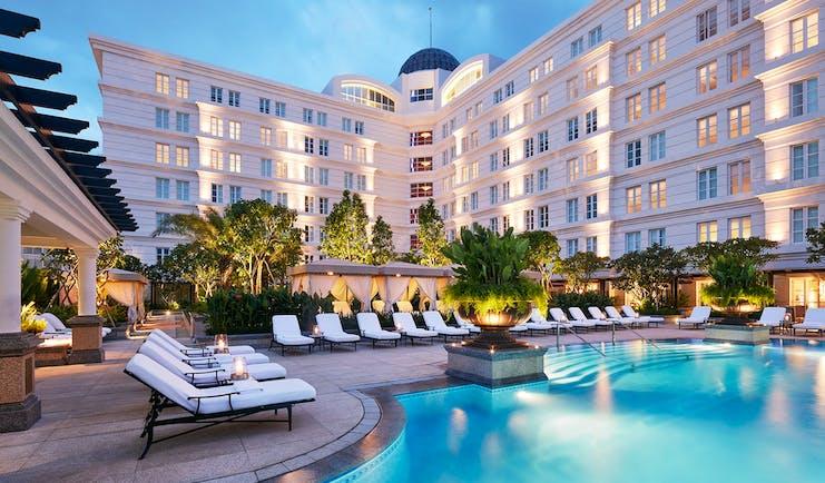 Park Hyatt Saigon pool, sun loungers, trees, hotel building in background
